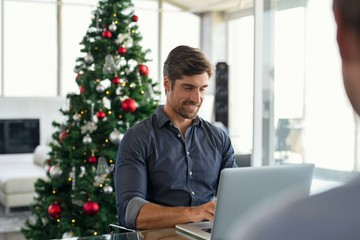 Man in front of Christmas tree using computer